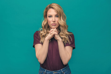 Young attractive blonde on a blue background. Beautiful woman posing on trendy background dressed in fashionable youth clothes.