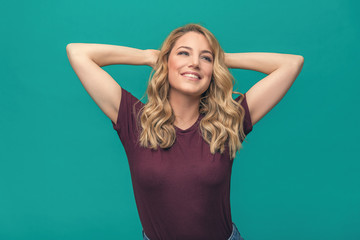 Attractive blonde rejoices with her hands behind her head, relaxing and smiling. Beautiful young woman on a blue background.