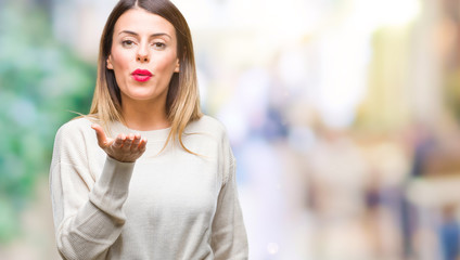Young beautiful woman casual white sweater over isolated background looking at the camera blowing a kiss with hand on air being lovely and sexy. Love expression.