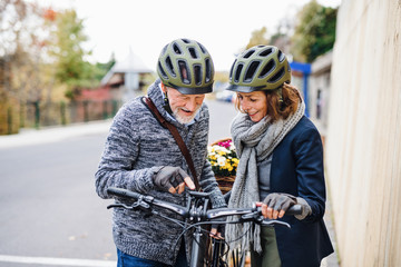 Active senior couple with electrobikes standing outdoors on pathway in town.