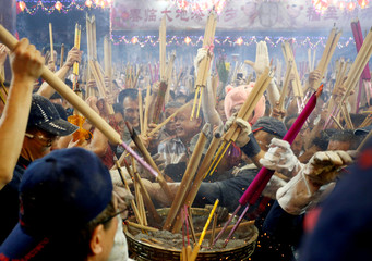 People rush to plant the first joss stick of the Lunar New Year of the Pig at the stroke of midnight at the Kwan Im Thong Hood Cho temple in Singapore