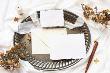 Styled stock photo. Winter, fall wedding, birthday table composition. Stationery mockup scene. Greeting cards, envelope, dry hydrangea flowers and calligraphy pen on silver tray. Flat lay, top view.