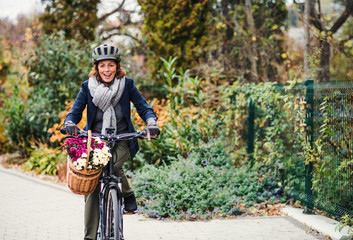 Active senior woman with electrobike cycling outdoors in town.