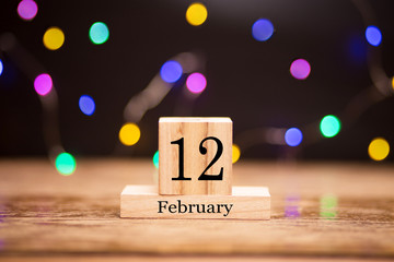 February 12th. Day 12 of february month set on wooden calendar at center of dark background with garland bokeh. Winter time. Empty space for text, mockup. Darwin Day. Day of Marriage Agencies