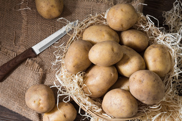 Potatoes in a basket on a wooden table. Rustic style