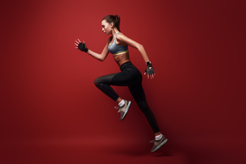 Do your best. Sportswoman jumping over red background, isolated