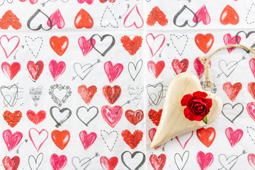 Wooden heart and red rose on paper for Valentines Day