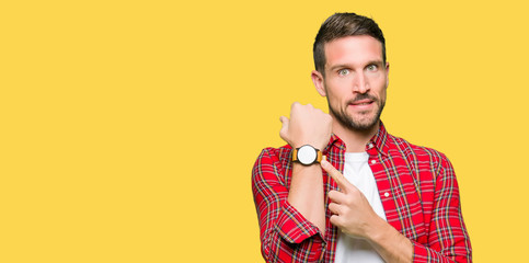 Handsome man wearing casual shirt In hurry pointing to watch time, impatience, upset and angry for deadline delay