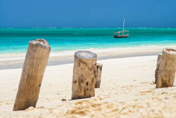 old wooden trunks in sand on the beach with view to boat at sea in Zanzibar in Tanzania