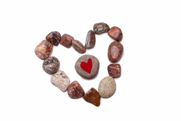 A heart shape image made with pebbles with a pebble with a heart shape painted on it in the center