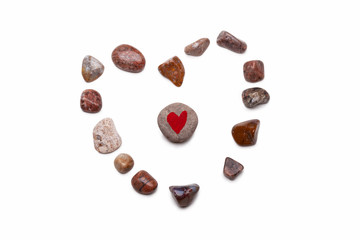 A heart made with pebbles, with a pebble with a red heart painted on it in the center