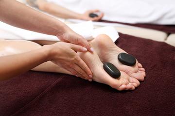 Masaż gorącymi kamieniami.  Kobiece stopy z kamieniami bazaltowymi, relaks w salonie spa.
