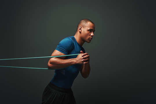 Pushing hard. Sportsman working out with resistance band over dark background