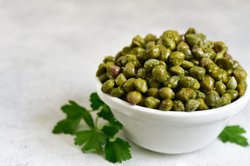 Marinated capers in a white bowl.