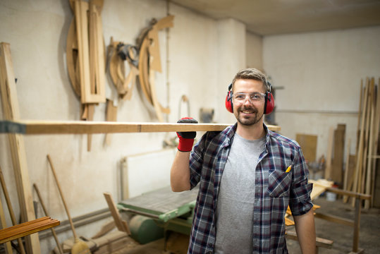 Portrait of young woodworker holding wood in his carpentry workshop.