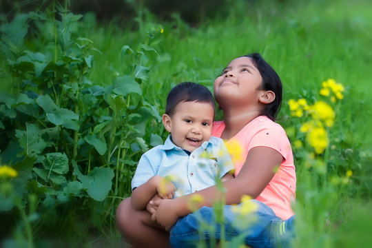 A cute girl looking up at the sky, expressing hope while holding her baby brother in her arms, in an outdoor field with flowers.