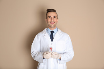 Male dentist holding tooth model on color background