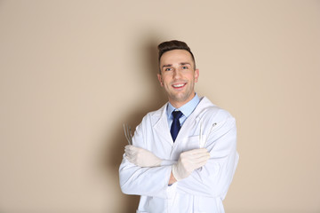 Male dentist holding professional tools on color background