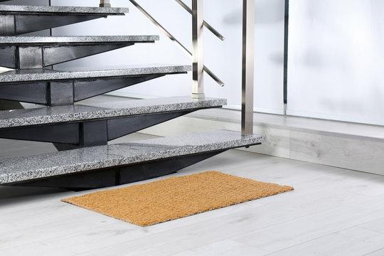 New door mat near stone stairs indoors