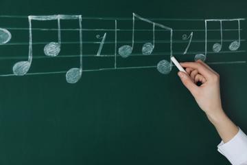 Woman writing music notes with chalk on blackboard, closeup