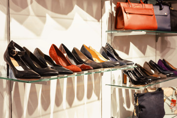 Shelves with fashionable leather shoes and bags in store