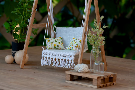 Dollhouse garden swing with white linen upholstery and pillows, A cozy sitting place for summer rest and recreation