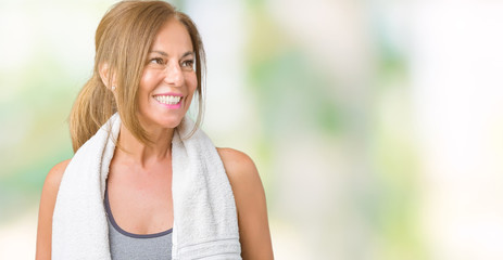 Beautiful middle age woman wearing sport clothes and a towel over isolated background looking away to side with smile on face, natural expression. Laughing confident.