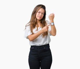 Young beautiful brunette business woman over isolated background In hurry pointing to watch time, impatience, upset and angry for deadline delay