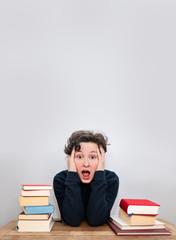 Verzweifelt gestresst überforderte Person Schüler mit Bücherstapel am Schreibtisch