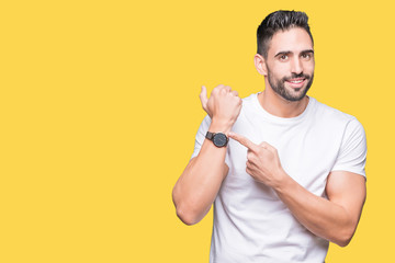 Handsome man wearing white t-shirt over yellow isolated background In hurry pointing to watch time, impatience, upset and angry for deadline delay