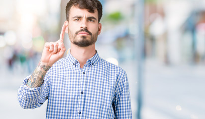 Young handsome business man over isolated background Pointing with finger up and angry expression