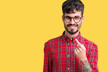 Young handsome man wearing glasses over isolated background Beckoning come here gesture with hand inviting happy and smiling