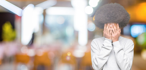 Young african american man with afro hair wearing sporty sweatshirt with sad expression covering face with hands while crying. Depression concept.