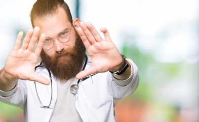 Young blond doctor man with beard wearing medical coat Smiling doing frame using hands palms and fingers, camera perspective