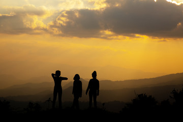Silhouette, group of happy girl playing on hill, sunset, summertime