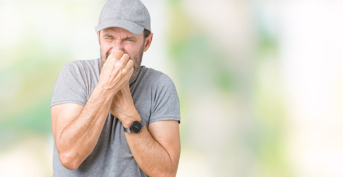 Handsome middle age hoary senior man wearing sport cap over isolated background smelling something stinky and disgusting, intolerable smell, holding breath with fingers on nose. Bad smells concept.