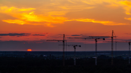 Several construction cranes on the background of colorful sunset sky
