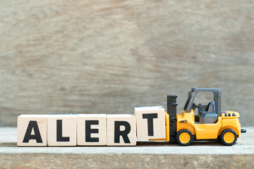 Toy forklift hold letter block t to complete word alert on wood background