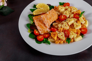 Plate in the form of a heart pasta with salmon and lemon