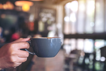 Closeup image of a hand holding a blue cup of hot coffee with blurred background in cafe