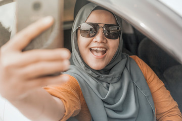 Muslim Lady Taking Selfie Photo With her Smart Phone in The Car