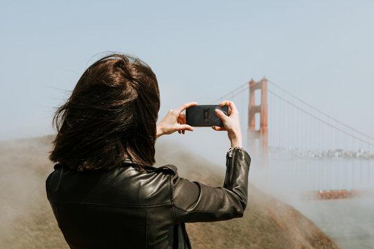 Woman taking a photograph of the Golden Gate Bridge, San Francisco