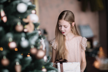 girl with a gift box standing near the Christmas tree .