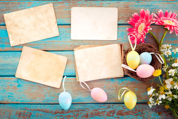 Colorful Easter eggs in nest with flower and empty old paper photo album on wood table  - concept of remembrance and nostalgia holiday in spring. vintage style