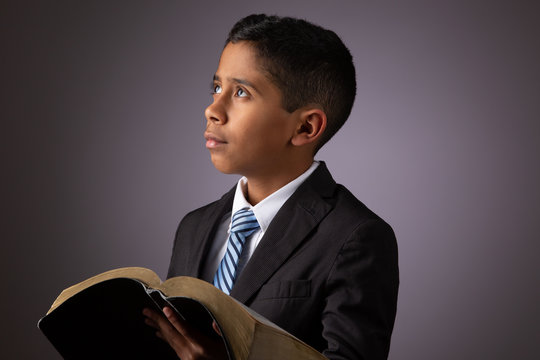 Little Hispanic Boy  Looking Away while Holding the Holy Scriptures, The Word of God, The Bible