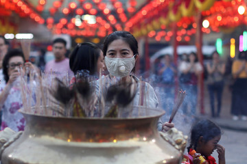 A woman lights incense while praying in a Chinese temple ahead of Lunar New Year in Chinatown in Bangkok