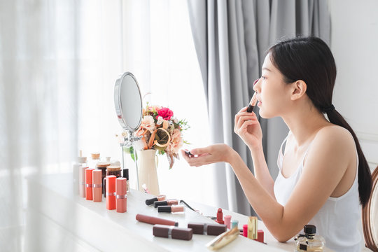 Young beautiful Asian woman applying cosmetics make up on her face, health beauty skin care and make up concept