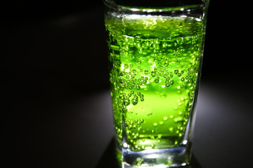 bright lucent green fizzy drink (lemonade, cocktail) with many small bubbles in dark closeup