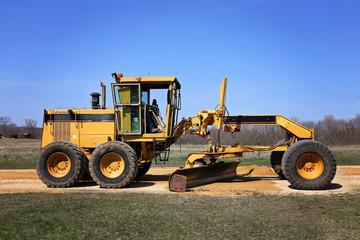 Big Road Grader Construction Truck Working on Rural Gravel Driveway