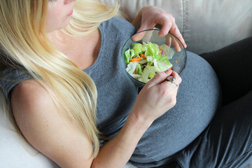 Healthy, Young, Pregnant Woman Sitting on Couch Eating Green Lettuce Salad